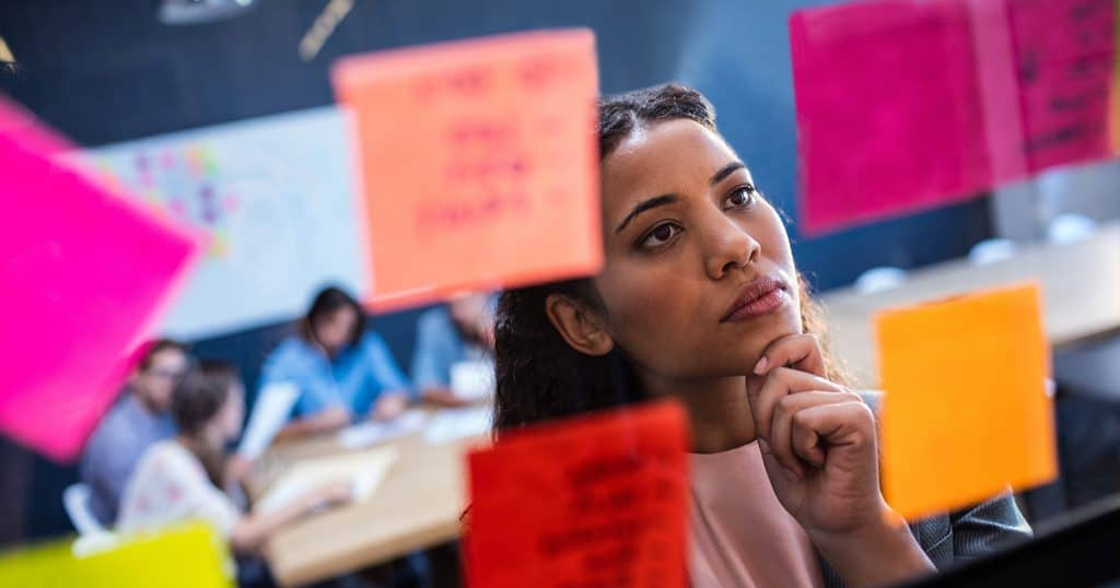 Young woman looking curious at glass wall with post-it questions